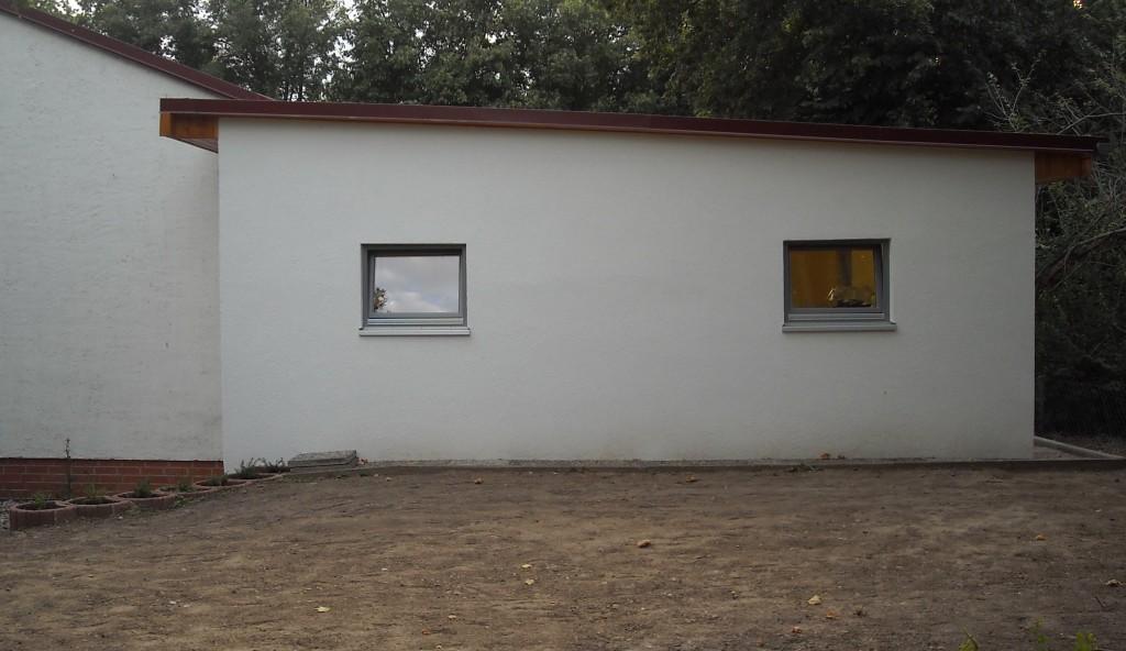 Blick von hinten auf den Alarmumkleideraum, Vordergrund Raseneinsaat, links die alte Fahrzeughalle